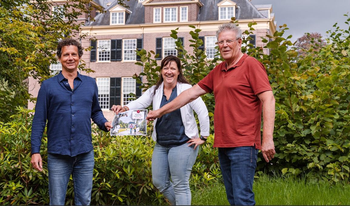 Jan ten Have (rechts) van Achterhoek Toerisme en Arno Ruis (links) van NBTC overhandigen de nieuwe wandelroute aan kasteelmanager Iris Littink (midden) van Huis Verwolde.
